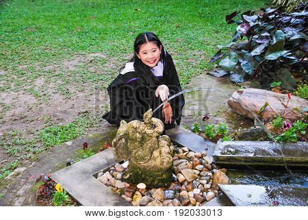 Cheerful Graduated Student Playing with Elephant Shape Fountain