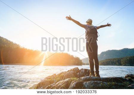 Woman Raises Her Arms Up Towards The Sun. To Dream Of Looking At The River.