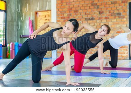 Fitness asian female group doing namaste yoga pose in row at the yoga class.