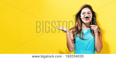 Young woman holding paper party mustache on a yellow background