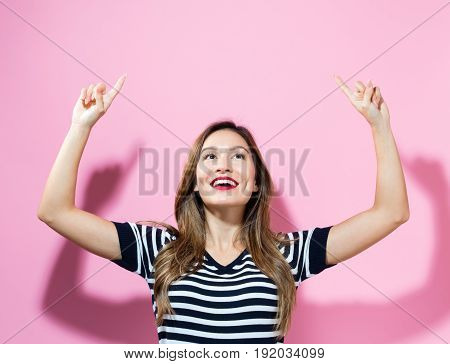 Happy young woman reaching and looking upwards