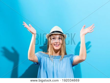 Young woman reaching and looking upwards on a blue background