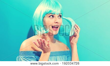 Beautiful woman in a bright blue wig holding a painted blue banana