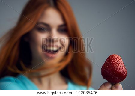 Woman with strawberry, cheerful woman, strawberry sweet, woman on gray background.