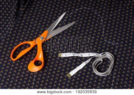Scissors Tailor And Inch, Centimeter Tape On A Background Of Blue Fabric With A Pattern