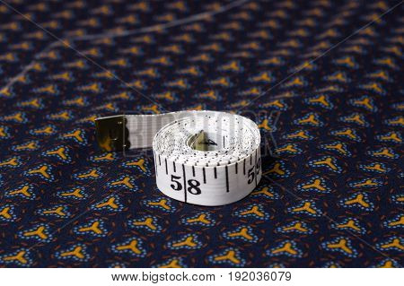 Inch, Centimeter Tape On A Background Of Blue Fabric With A Pattern