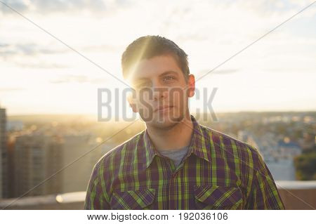 Portrait of a roofer top man on the roof at sunset at sunset. Courage and adrenaline. Loneliness and calmness.