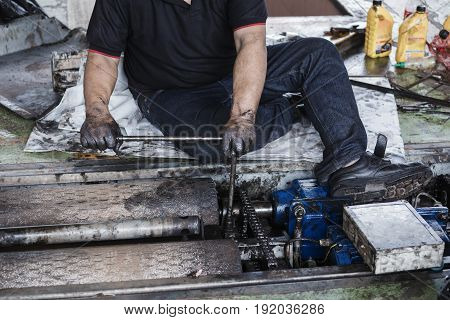 Repairman Holding A Wrench And Tighten And During Maintenance Work Of Machine