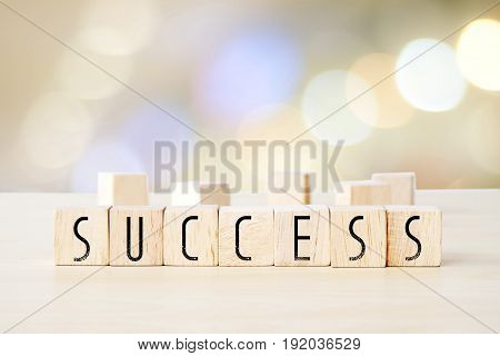 Success word on wooden cubes over blur background business concept