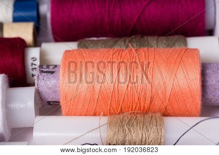 Various multicolored used sewing threads in a box stacked in a row