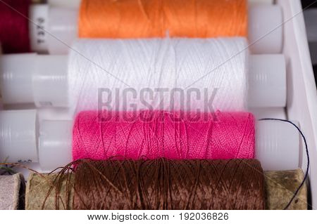 Various Multicolored Used Sewing Threads In A Box, Stacked In A Row