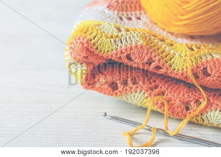 Crocheted handmade background. Knitted fabric in a yellow rose color Ball of threads and crochet hook. Vintage toning copy space