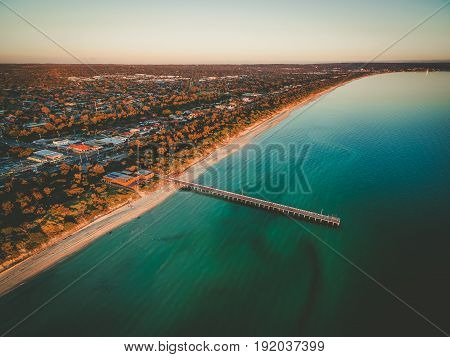 Aerial View Of Long Wooden Pier Stretching Into Turquoise Shallow Ocean Water And Beautiful Suburban