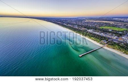 Aerial Panorama Of Beautiful Ocean Coastline Beaches And Suburbs At Dusk.