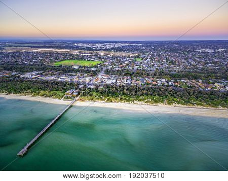 Aerial View Of Long Wooden Pier Stretching Into Shallow Ocean Water And Coastal Suburban Houses In M