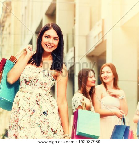 Portrait of beautiful smiling woman posing after shopping with her friends, A picture with toning and a square relation of the sides