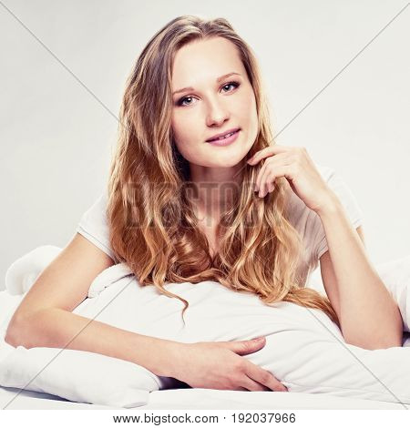 Portrait of attractive happy blonde woman lying in bed at home, A picture with a tint and a square relation of the sides