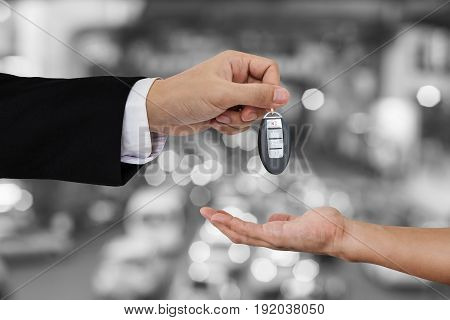 Hand holding and receiving car key remote with Bokeh of car traffic background
