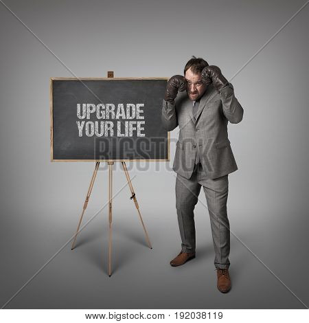 Upgrade your life text on blackboard with businessman with boxing gloves
