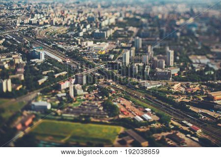 True tilt-shift view from very high above of railway with several tracks aerial view of railroad station in focus surrounded by defocused residential districts and industrial zone Moscow Russia