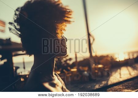 Silhouette of young Brazilian girl with curly afro hair illuminated by orange light looking on coastline while standing on embankment on windy summer evening with beach caffe in defocused background