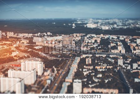 True tilt-shift view from very high point of highway in focus and surrounding residential districts in defocused background and foreground view of modern city from very high point on sunny day