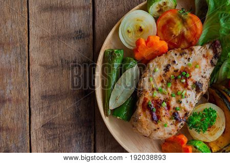 Homemade chicken breast barbecue on wood plate served with grilled vegetables. Delicious chicken barbecue and grilled vegetables for lunch or dinner. Roast chicken breast on rustic wood table. Chicken barbecue or pork steak.