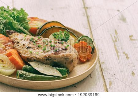Homemade chicken breast barbecue on wood plate served with grilled vegetables. Delicious chicken barbecue and grilled vegetables for lunch or dinner. Roast chicken breast on rustic wood table. Chicken barbecue in extremely underexposed.