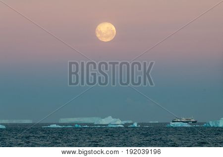 The Full Moon is rising over the iceberg filled Weddell Sea. Antarctica.