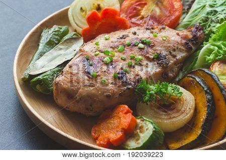 Homemade chicken breast barbecue on wood plate served with grilled vegetables. Delicious chicken barbecue and grilled vegetables for lunch or dinner. Roast chicken breast on granite table. Piece of chicken barbecue or pork steak.