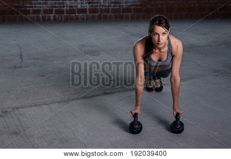 Fitness concept. Woman athlete push ups with dumbbells on the floor with copy space