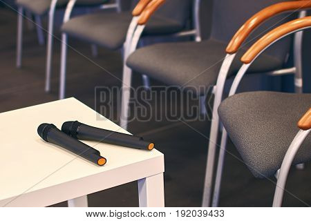 Two black microphones on the table at conference