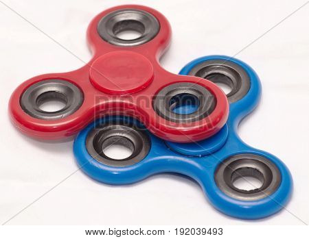 A red fidget spinner stacked on top of a blue one