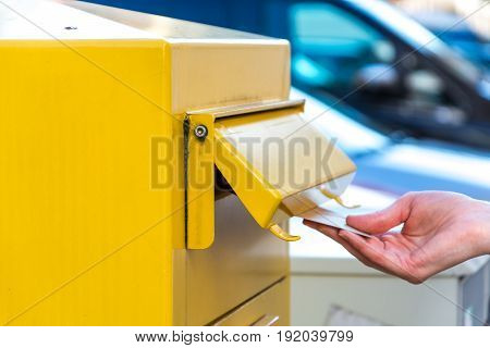 Throwing A Letter In A Yellow Mailbox