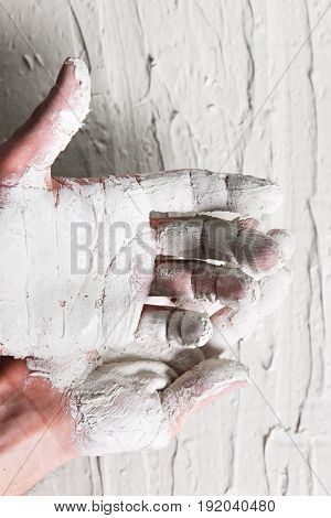Plastering work, building. Dirty worker hands in white stucco on rough background, flat lay.