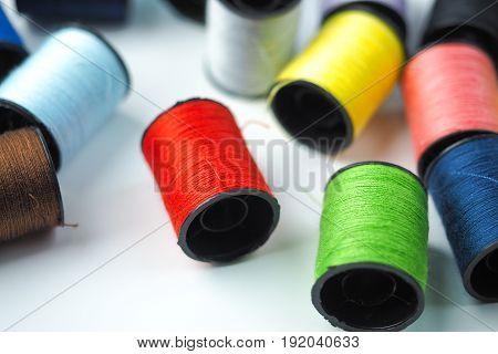 Colorful sewing thread reels on white background