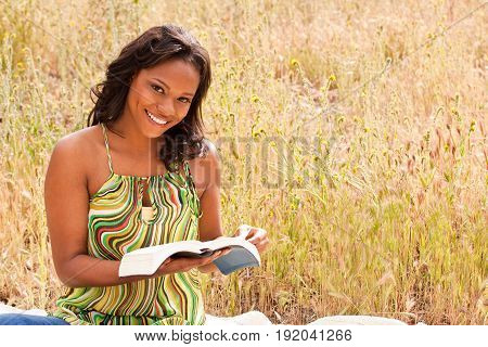 African American woman sitting in a field.