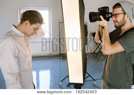 Photographer shooting handsome model. Casual man with camera focusing on male model posing in studio. Production of fashion commercials backstage