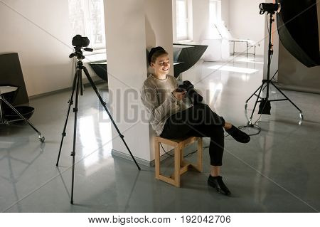 Photographer in studio enjoy pictures on camera. Casual young artist looking at result of photo session and happy of it. Professional creative people, inspiration, art, business, talent concept