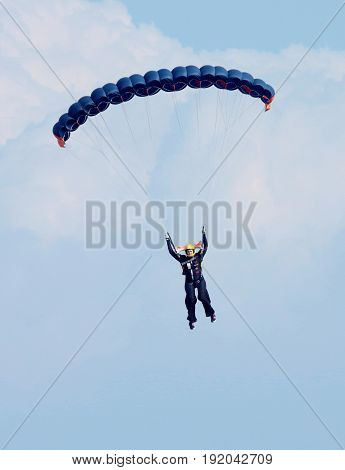 Female Sky Diver With Bright Blue Open Parachute