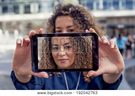 pretty young woman take a selfie with smart phone in the heart of a capital city