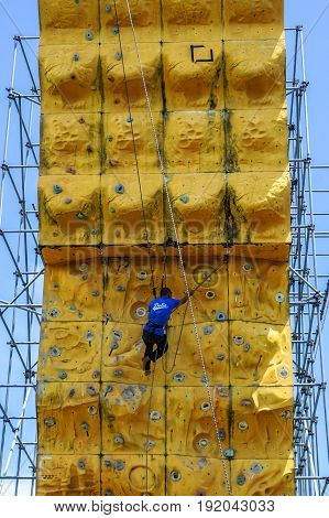Labuan,Malaysia-May 21,2017:Male climber with safety equipment climb on yellow climbing wall in Labuan,Malaysia.It is an activity in which participants climb up or across artificial rock walls