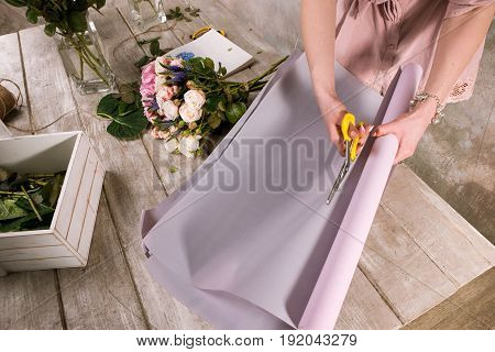 Florist wrapping bouquet of rose flowers. The decorator works in a greenhouse with a pink bouquet. Floristic workshop, skill, decor, small business concept