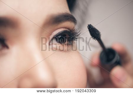 Close-up Portrait Of Beautiful Girl Touching Black Mascara To Her Lashes