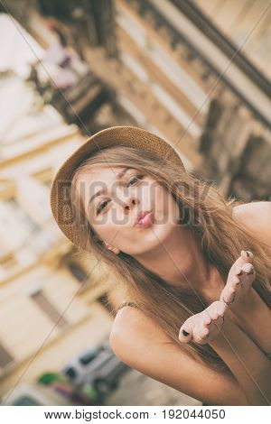 Young beautiful girl sending air kiss on the street.