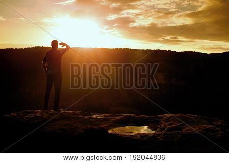 Runner On The Peak. Man In His Target With Hand At Eyes. Hiker In Black Running Trousers And Shinnin