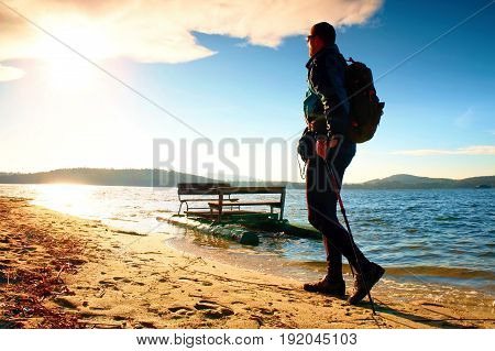 Tourist On Beach At Old Paddle Boat. Man With Poles  In Warm Sporty Clothing At Sunset. Autumn Weath