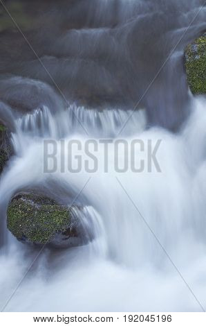 Close up of rushing river water flowing over mossy rocks