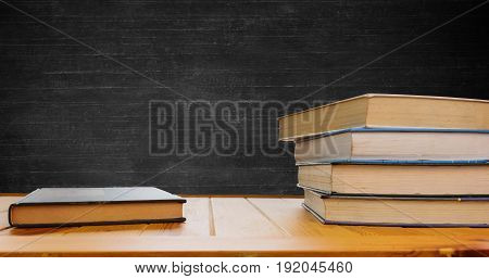 textbooks on school desk with blackboard for background