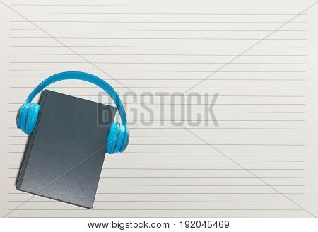 book and headphone over white paper line